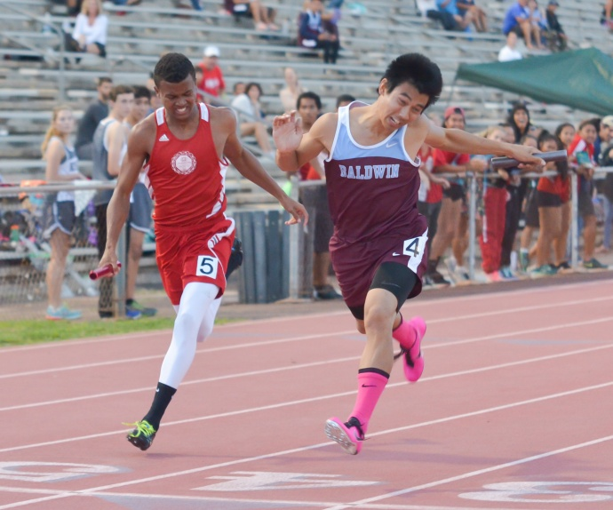 Baldwin's Bailey Kaopuiki (right) nips Lahainaluna's Emerson Liburd at the finish of the boys 4 x 100 relay Friday. The Bears were timed in 45.59 seconds to the Lunas' 45.72 seconds. Photo by Rodney S. Yap.