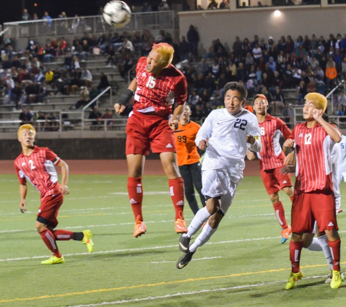 Kalani High School defender Toshi Kosins (9) heads this corner kick from Kamehameha Maui's Nainoa Silva out of the Warriors' scoring area in the closing stages of their match Saturday at Pukalani. Photo by Rodney S. Yap.