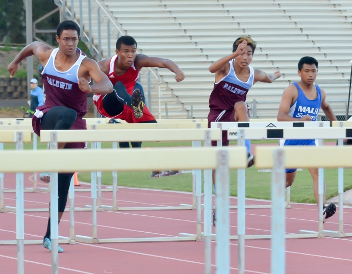 Baldwin's La'akea Kahoohanohano-Davis takes a solid lead over Lahainaluna's Emerson Liburd. But the Lunas' hurdler caught Kahoohanohano-Davis midway through the 110-meter race en route to recording his fastest time ever in 14.57 seconds. Photo by Rodney S. Yap.