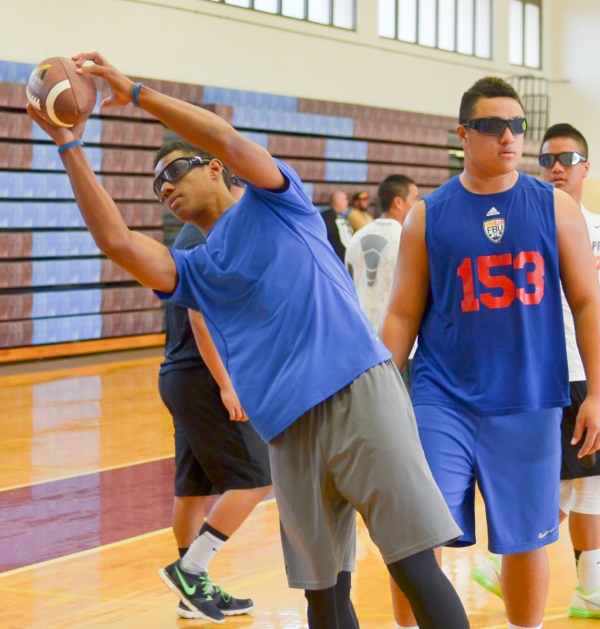 Baldwin junior Laakea Kahoohanohano-Davis catches a ball wearing NIKE strobes. Maui High's Jonathan Pono Lolohea (153) awaits his turn. Photo by Rodney S. Yap.
