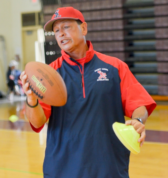 Saint Louis School's assistant coach Vince Passas explains the proper grip to throwing a football Saturday at Baldwin High School Gym, Photo by Rodney S. Yap.