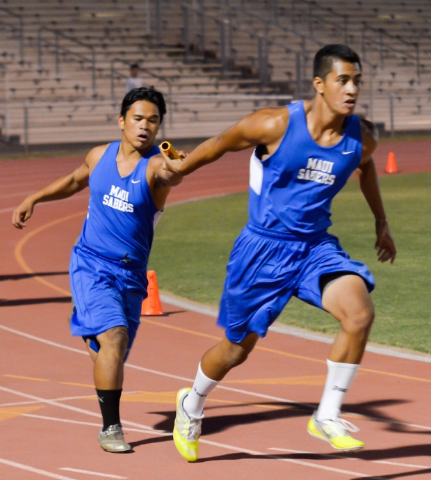 Maui High's Lucas Ibanez hands off the baton to Grayson Biga   in the boys 400-meter weightman's relay Friday. The Sabers won the race with Moana Vainikolo running the first leg and Arven Lacaden running the second leg. Photo by Rodney S. Yap.