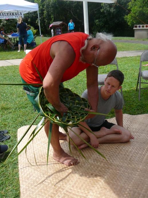 Bolly Helekahi helps a visitor make a coconut leaf hat. Photo credit: Haleakalā National Park.