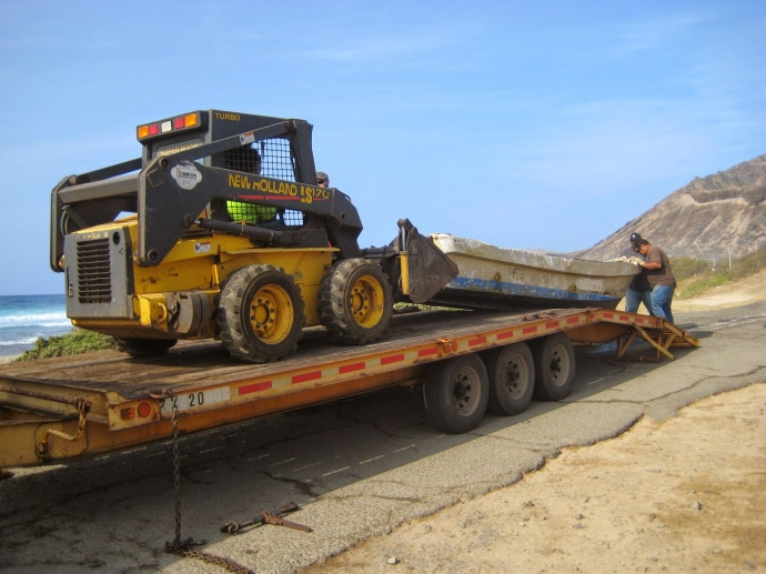 DLNR Land maintenance crew hauls the skiff from Alan Davis beach onto a trailer today (4-23-15). Photo by DLNR.
