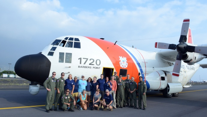Crew members from Coast Guard Air Station Barbers Point, National Oceanic and Atmospheric Administration and the Department of Land and Natural Resources pose for a photo after safely loading two female Hawaiian Monk Seals onto an HC-130 Hercules airplane in Kona, Hawaii, March 18, 2015. Coast Guard crew members, NOAA, DLNR and the U.S. Fish and Wildlife Service partnered together to transport two rehabilitated Hawaiian Monk Seals to Midway Atoll where they would be transferred via ship to Kure Atoll State Wildlife Sanctuary. (U.S. Coast Guard photo by Petty Officer 2nd Class Tara Molle) NMFS permit #932-1905-01/ma-009526-1