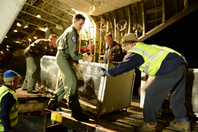 Crew members from Coast Guard Air Station Barbers Point assist with offloading a Hawaiian Monk Seal off an HC-130 Hercules airplane at Midway Atoll, March 18, 2015. Coast Guard crew members, National Oceanic and Atmospheric Administration, U.S. Fish and Wildlife Service and the Department of Land and Natural Resources partnered together to transport two rehabilitated Hawaiian Monk Seals to Midway where they would be transferred via ship to Kure Atoll State Wildlife Sanctuary. (U.S. Coast Guard photo by Petty Officer 2nd Class Tara Molle) NMFS permit #932-1905-01/ma-009526-1