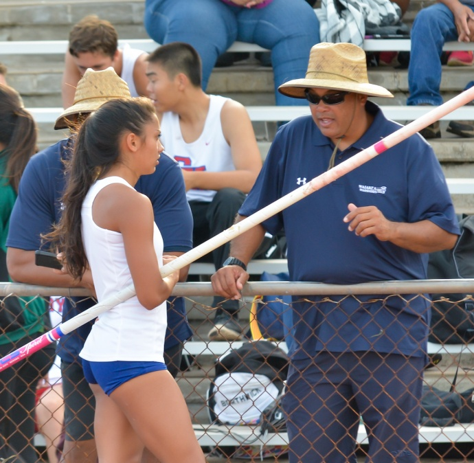 Waiakea's vault coach Sherman Viernes talks with Darien Calicdan in between jump attempts of the girls pole vault Thursday. Photo by Rodney S. Yap.