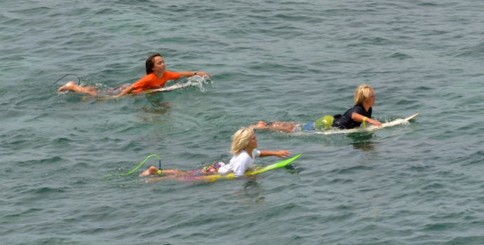 Three surfers paddle out before the start of their heat Saturday at Hookipa Beach Park. Photo by Rodney S. Yap.