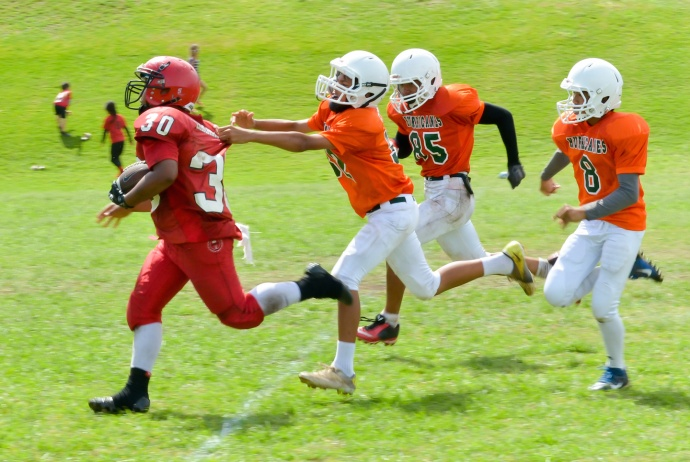 Lahaina is running back (30) tries to elude the Wailuku pursuit as he runs toward the end zone. Photo by Rodney S. Yap.