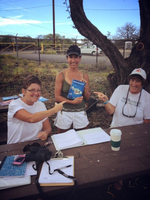 Margo pictured (far right at the volunteer information station helping a visitor) while she was volunteering at the  ʻĀhihi Kīnaʻu Natural Area Reserve as a volunteer interpretive guide.  Courtesy photos.