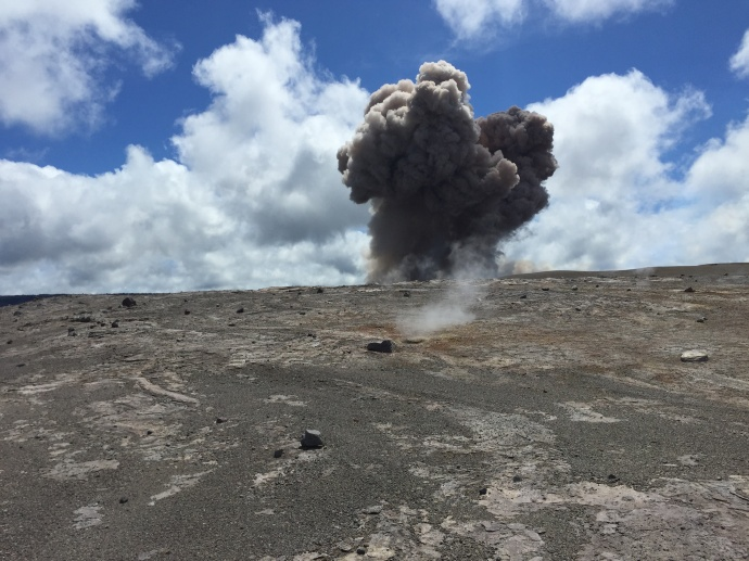 A rockfall from the wall of Halemaʻumaʻu Crater impacted the lava lake around 10:20 am, triggering an explosion of spatter and smaller particles. HVO geologists working on the far side of the crater captured the initial moments of the plume rising. The explosion deposited a large amount of spatter around the closed Halemaʻumaʻu visitor overlook. Photo courtesy USGS/ Hawaiian Volcano Observatory.