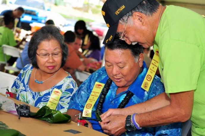 """Blossoms for the Brave"" - Mayor Arakawa and wife Ann learning how to make a Ti leaf lei (5.24.2013) File photo courtesy County of Maui."