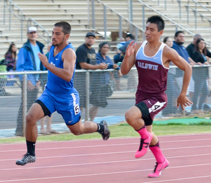 Baldwin's Baily Kaopuiki battles Maui High's Justin Cravalho around the turn of the boys 200-meter dash Saturday. Photo by Rodney S. Yap.
