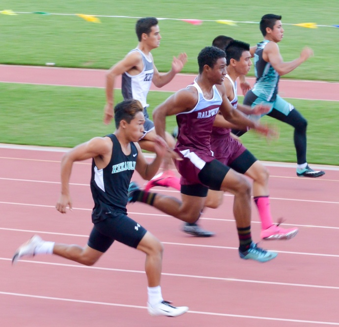 Baldwin's Bailey Kaopuiki (pink socks) won the boys 100-meter dash, but not until he broke away from the pack after suffering a slow start. Photo by Rodney S. Yap.