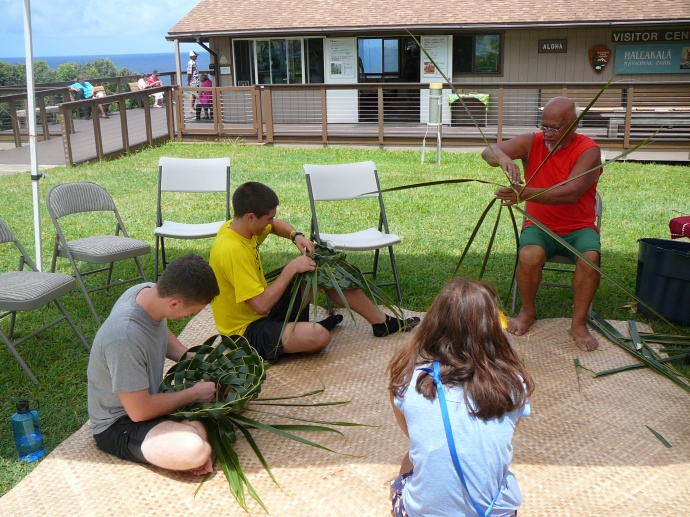 Bolly Helekahi helps a visitor make a coconut leaf hat. Photo credit: Haleakalā National Park.