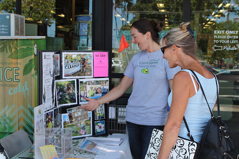 MMN Community Relations Manager Jen Cox speaks with a Whole Foods Market customer about MMN's programs during the April 1 5% Community Support Day. Photo courtesy of Whole Foods Market Kahului.