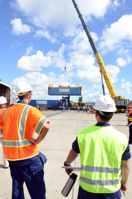 Coast Guard crew members observe crane operations during the Hawaii Alternate Port Concept Full Scale Exercise at Joint Base Pearl Harbor-Hickam, June 5, 2015. The purpose of this exercise is to prepare the state, Navy, Coast Guard and industry response partners for their roles during a major catastrophic event that closes the Port of Honolulu and requires the activation of the Alternate Port in Pearl Harbor. (U.S. Coast Guard photo by Petty Officer 2nd Class Tara Molle)