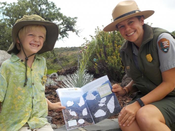 "Eliot shows Ranger Katelyn his favorite activity in the book, ""Snail Trail."" Photo credit: Haleakalā National Park."