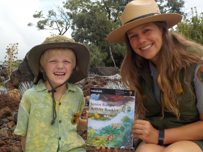 Eliot Carter and Ranger Katelyn Thomson display the park's new Junior Ranger Activity Book. Photo credit: Haleakalā National Park.