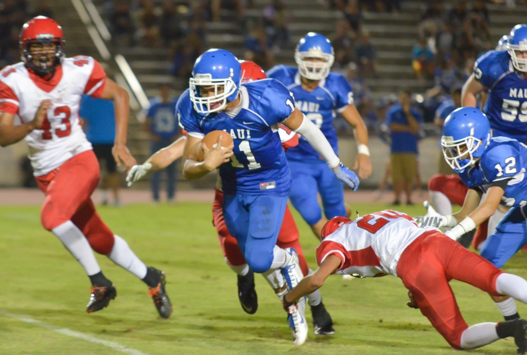Maui High's Jayden Wilhelm (11) looks for running room against the Lunas' defense. Photo by Rodney S. Yap.