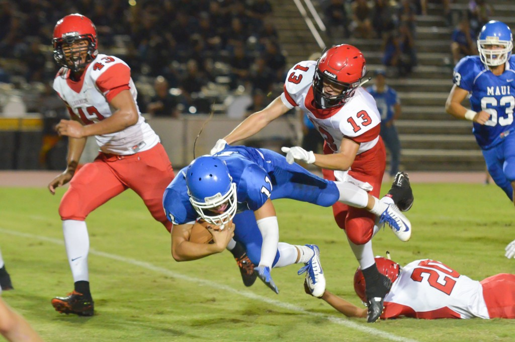Maui High's Jayden Wilhelm (11) is tripped up by Lahainaluna's Laakea Shim (20). Photo by Rodney S. Yap.