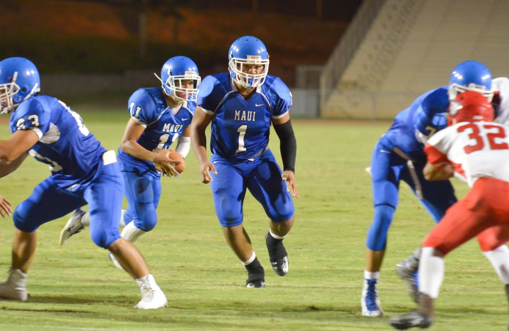 Maui High's Jayden Wilhelm (11) looks for running room behind running back Soane Vaohea (1). Photo by Rodney S. Yap.