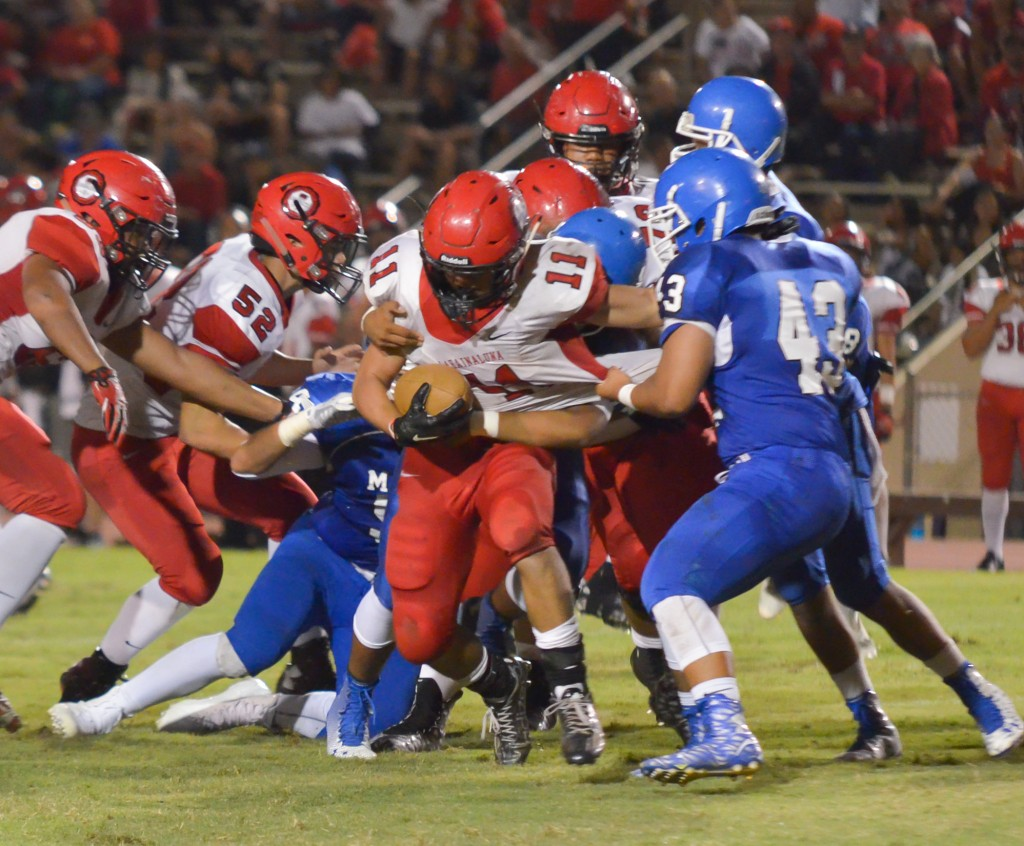 Lahainaluna's Justice Tihada (11) runs for tough yards against the Sabers' defense. Photo by Rodney S. Yap.