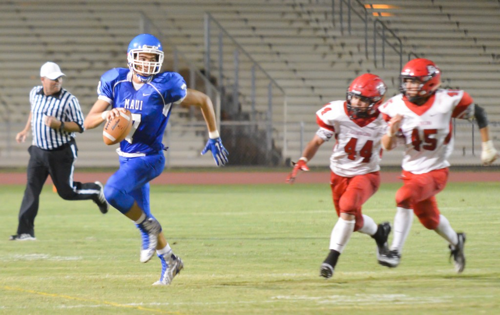 Maui High quarterback Austin Hoe runs from the Lahainaluna pursuit led by Lahainaluna's Ivan Upfold-Pante (44) and Ammon Walters (45). Photo by Rodney S. Yap.