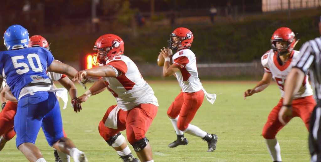 Lahainaluna quarterback Etuati Storer (2) looks for a teammate open in the end zone. Photo by Rodney S. Yap.