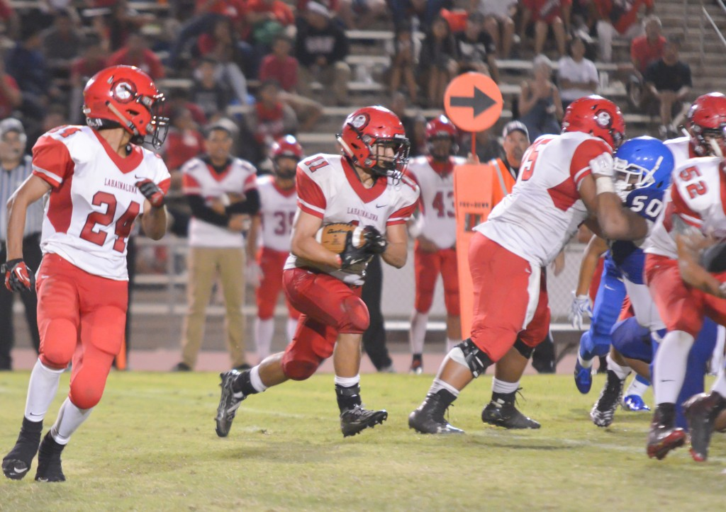 Lahainaluna's Justice Tihada (11) looks for running room. Photo by Rodney S. Yap.