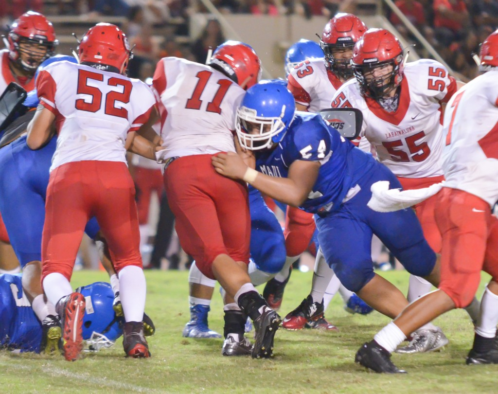 Maui High's Mahonri Anitema (55) puts the pads on Lahainaluna's Justice Tihada (11). Photo by Rodney S. Yap.