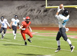 King Kekaulike's Brandon Soriano (22) squeezes this pass from quarterback Cameron Russell (5). Photo by Rodney S. Yap.