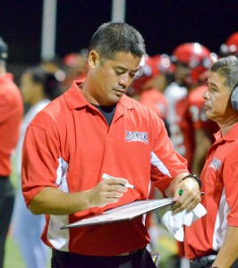 Lahainaluna co-head coach and offensive coordinator Garret Tihada draws up a play during a break in the game Saturday. Photo by Rodney S. Yap.