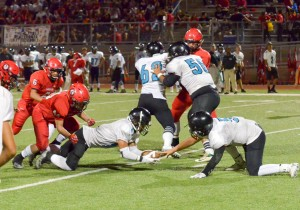 Kekaulike's Kawika Akahi (11) hauls in this loose ball in the backfield. in front of quarterback Cameron Russell. Photo by Rodney S. Yap.