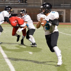King Kekaulike quarterback Cameron Russell rolls to his left in search of a receiver. Photo by Rodney S. Yap.