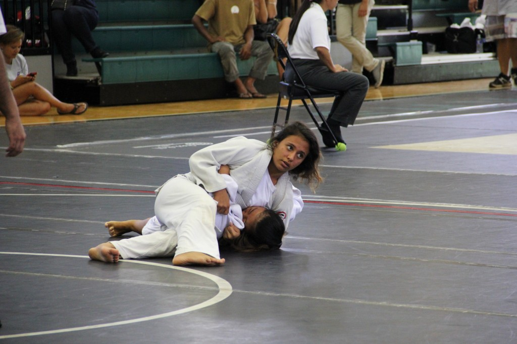 Hiialoa Palakiko of Makawao Hongwanji keeps an eye on the clock as she pins Kara Yoshiyama of Hilo Hongwanji. Palakiko won the match by ippon. Photo credit: Cy Yoshizu