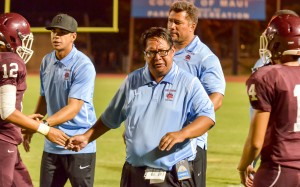 Baldwin head coach Pohai Lee and offensive assistants Lemoa Tua (back) and Colten Quinabo (left) congratulate members of the offensive unit after a Baldwin touchdown Friday. Photo by Rodney S. Yap.