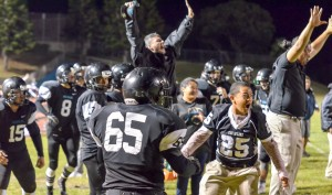 King Kekaulike's coaches and players celebrate a huge catch at the opposite side of the field that helped Na Alii score their first touchdown of the game. Photo by Rodney S. Yap.