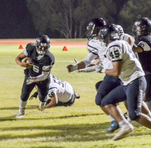 King Kekaulike quarterback Cameron Russell looks for running room in traffic near the goal line Saturday. Photo by Rodney S. Yap.