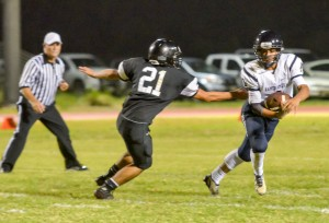 Kamehameha Maui quarterback Kainoa Sanches manages to avoid the grasp of King Kekaulike's Rilee Peters. Photo by Rodney S. Yap.
