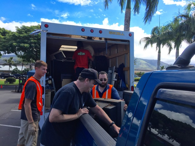 Rich Lynch (from left), Angus McKelvey and Scott Matovich help unload a TV