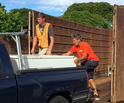 Rich Lynch (left) and Peter Faust help unload a refrigerator