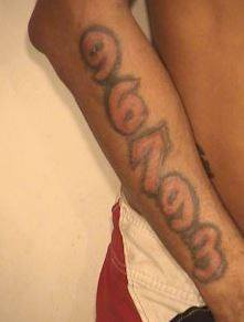 "Shaun M. Dennis has the following tattoos: ""Gangster holding a gun"" on his right chest and ""96793"" on his right forearm."