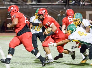 Lahainaluna's Donovan Defang (21) follows the block of teammate Junior Moala (75) up the middle against Kaimuki on Saturday. Photo by Rodney S. Yap.