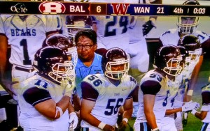 Baldwin breaks the huddle on the sidelines with head coach Pohai Lee and runs in for the final play of the game. Photo from OC16 broadcast.