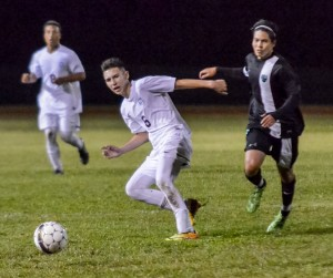 Baldwin's passes the ball to a teammate on the sidelines as King Kekaulike's Ian Almeida defends. Almeida scored Na Alii's first goal in the 38th minute en route to their 2-0 victory over the Bears on Friday. Photo by Rodney S. Yap.