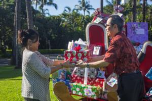 Joyce Natividad, Program Secretary for Maui Child & Family Services receives the annual donation of gifts by the Mākena Beach & Golf Resort from Kiyoshi Terada (right), sales & marketing coordinator at Mākena Beach & Golf Resort.