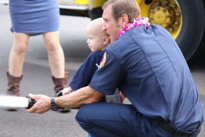 Trucker Dukes shooting water with his dad, firefighter Joshua Dukes outside of the Kahului Fire Station. Photo by Wendy Osher.