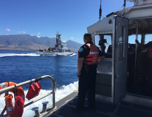 Officer Eric Vuong of Hawaii Department of Land and Natural Resources observes the USCGC Kiska (WPB 1336) and keeps a lookout for whale activity near Maui, Feb. 11, 2016. DLNR and the Coast Guard conducted safety and compliance boardings on recreational and commercial vessels to inform the public of the requirements to avoid coming too close to whales or impeding the whales' path. (U.S. Coast Guard photo by Chief Petty Officer Sara Mooers/Released)