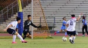 Kamehameha Maui's Paytin Ayau (10) shoots the game-tying goal past Baldwin goal keeper Friday at War Memorial Stadium. The Warriors' Brennan Joaquin (11) looks on. Photo by Rodney S. Yap.